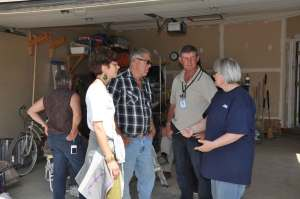 -Janet Plenert, MDS Region V Manager, Peter Goertzen and Garry Wiens, MDS Alberta Unit members, talk with Ms. Wall, a homeowner in Black Diamond.
