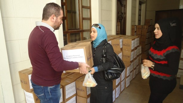 n Damascus, a woman accepts a box of food supplied by MCC through its partner, the Syrian Orthodox Church. She is not identified for security reasons. Photo courtesy of the Syrian Orthodox Church