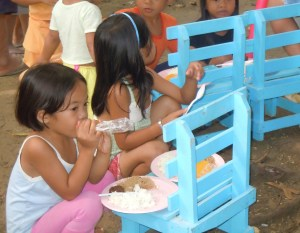 Children in the Philippines eat a meal provided by the Gleaners.