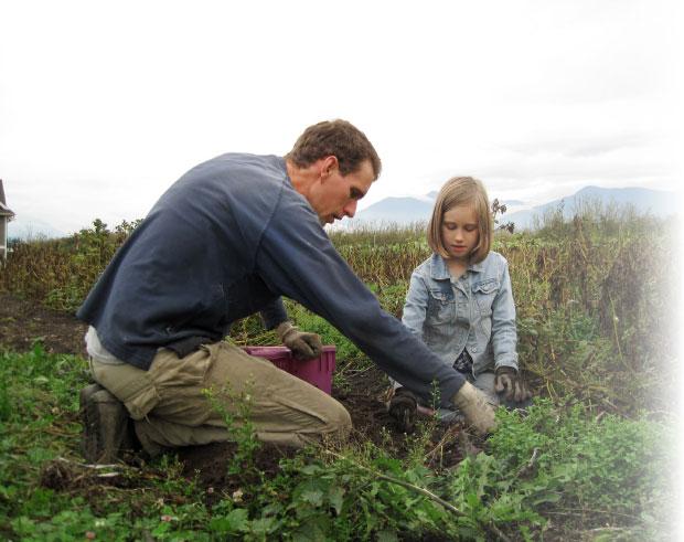 Abundant Acre farmer and Highland Community Church member Andy Abrahams harvests potatoes with his daughter. Photo: Cara Abrahams