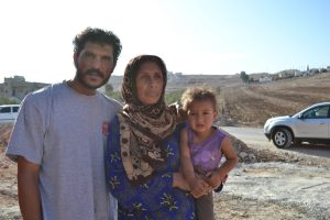 Abdel el-Razek, his wife, and their youngest child outside their tent near Irbid, Jordan.