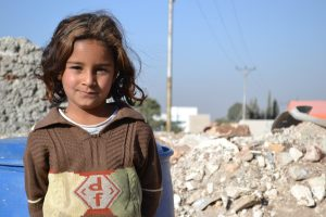 Syrian refugee Angeline el-Razek, standing outside the tent her family calls home on the outskirts of Irbid, Joran.