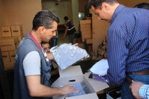 A Canadian government-funded project with MCC's partner organization Middle East Council of Churches (MECC) provides household items for internally displaced people and vulnerable host communities in Syria's Daraa Governorate. A MECC staff person shows the contents of an aid kit to a recipient who was randomly selected to give his opinion about the items being distributed. Names are not used for security reasons. (MECC photo/Jalal Al-Eid)