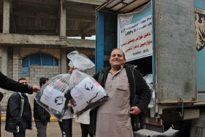Ismael shows the bags of winter clothing he received from MCC through its partner Zakho Small Villages Project in Iraq. His family was among those displaced more than a year ago by the Islamic State group. His last name was withheld for security reasons. (MCC Photo)
