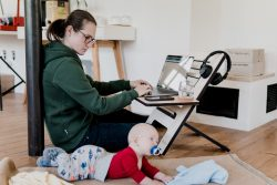 work-life balance: woman working on computer with baby next to her