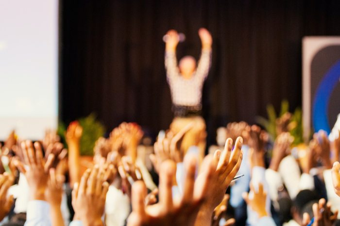Closeup of hands being held in a crowd, facing a speaker at a conference, holding their hands up