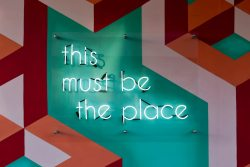A neon sign that says 'this must be the place' on a colorful geometric wall, symbolizing a business that understands the keys to attracting top talent