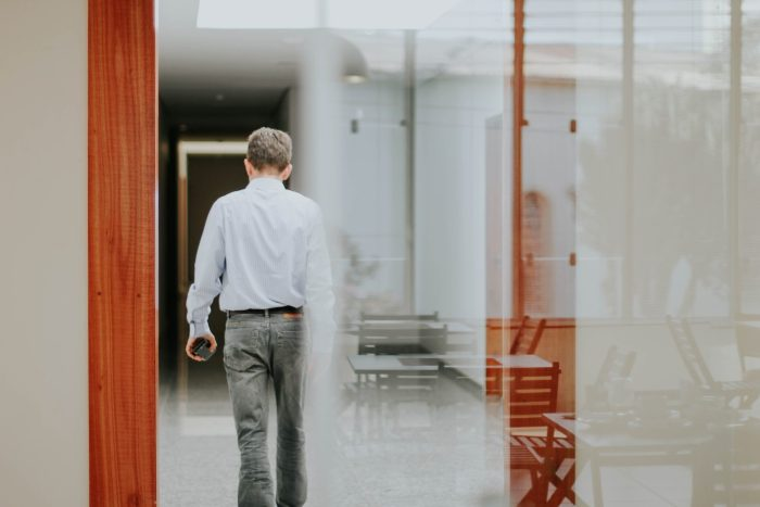 man in an office from behind, walking away with his phone in his hand