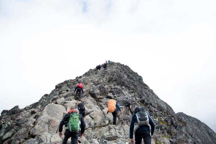 backpackers climbing mountain, demonstrating team building