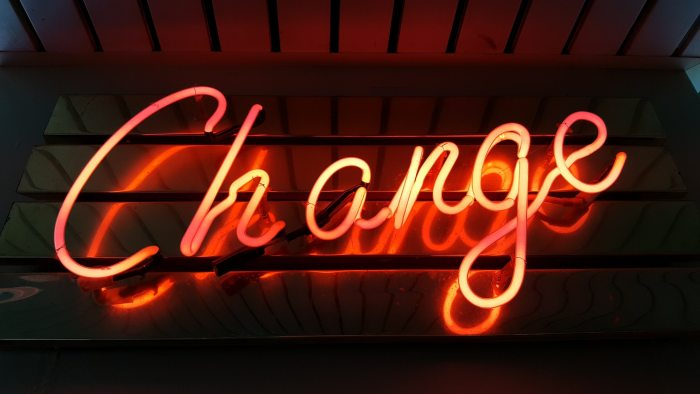 """orange neon sign reading """"change"""" in cursive, representing change management: one of the top hr priorities for 2021 and beyond"""