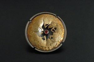 Fran Grinels created a brooch where the center is cut out and looks like a Rorshach design with a stone tube set in the center