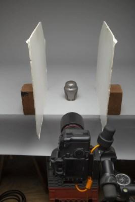 Metal owl vessel on tabletop with white foam core bounce boards on each side