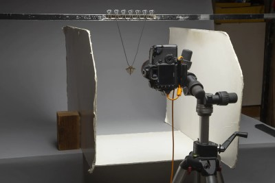 Camera on tripod aimed at necklace hanging off a crossbar; two white poster board pieces on each side to bounce light