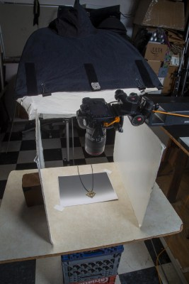 Camera extended with copy stand and tripod fitting over jewelry