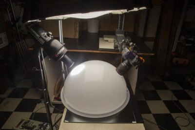 White acrylic Cloud Dome setup with 2 holes at 45 degree angles to the object in the dome; one hole has spotlight and 2nd hole has camera lens