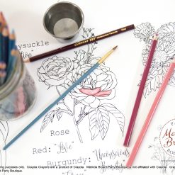 Watercolor pencils and paint brushes on the floral coloring table runner