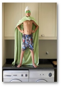 Boy with towel cape on washing machine