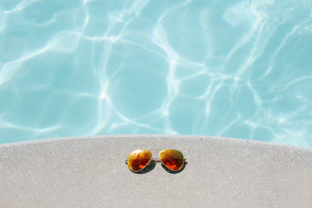 Sunglasses on the sand near water