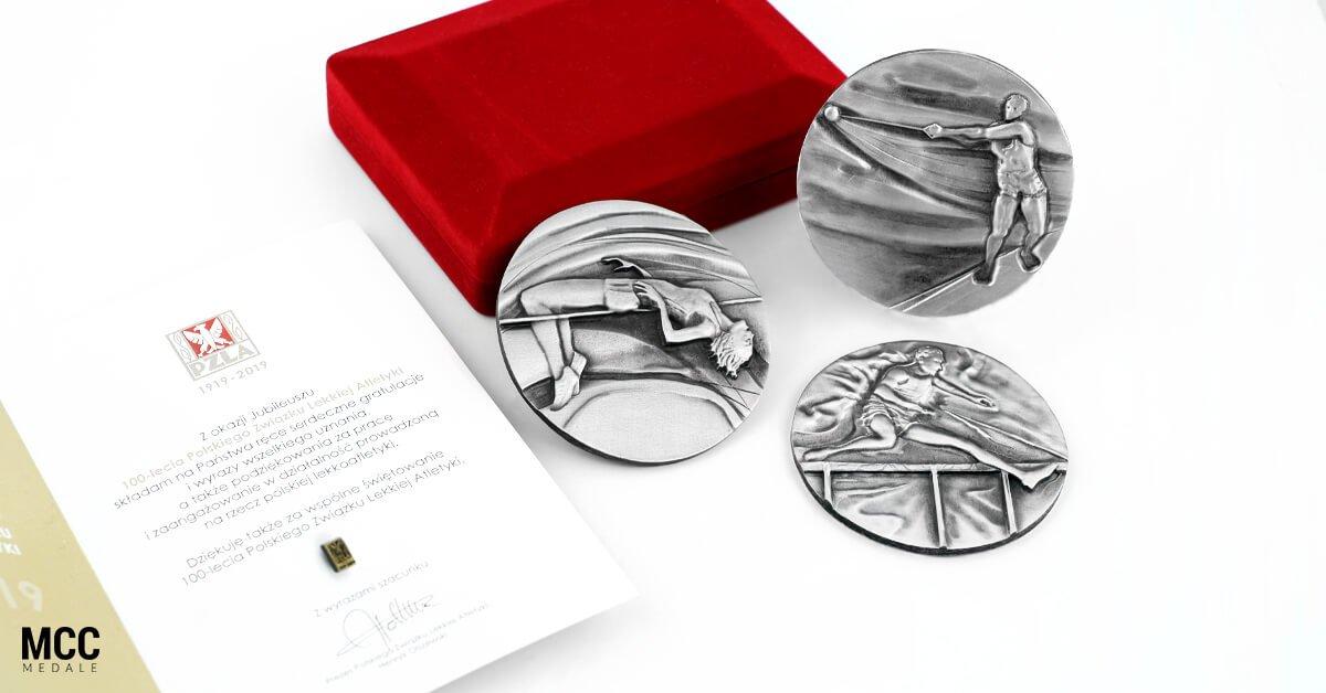Zestaw pamiątkowych medali oraz pinsów przygotowanych przez MCC Medale na 100 lecie PZLA