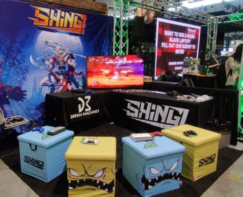 Stoisko gry indie Shing! z pinsami wyprodukowanymi przez MCC Medale