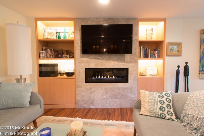 Horizontal fireplace in tile surround with TV above