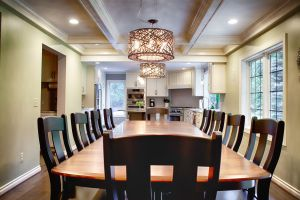 Looking down wood dining room table into kitchen with white cabinets