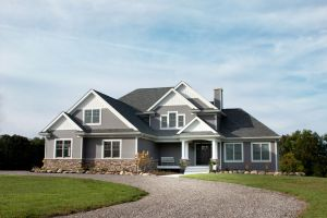 Two story home with grey siding, white trim, and stone detailing
