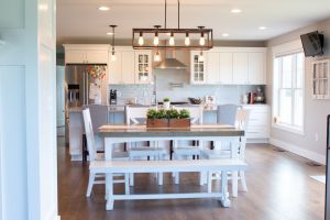 White farmhouse table with kitchen beyond