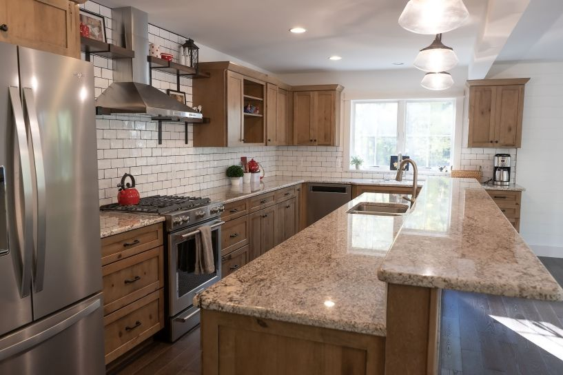 Rustic wood cabinets in a kitchen with subway tile walls