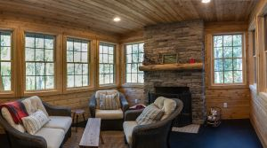 Cedar paneled sunroom with stone fireplace