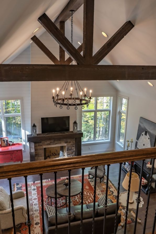 View of fireplace is framed by guard rail and timber trusses