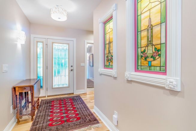 Light and airy entry hall with stained glass inserts on right wall