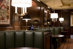 Green leather booths with rich wood paneling