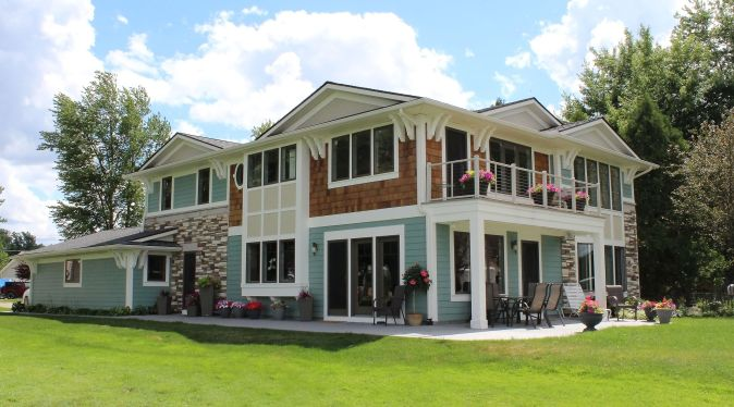 Two-story home with stone, siding, shakes, and white trim