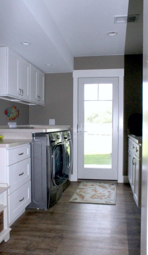 Glass entry door with laundry cabinets and appliances on left hand side