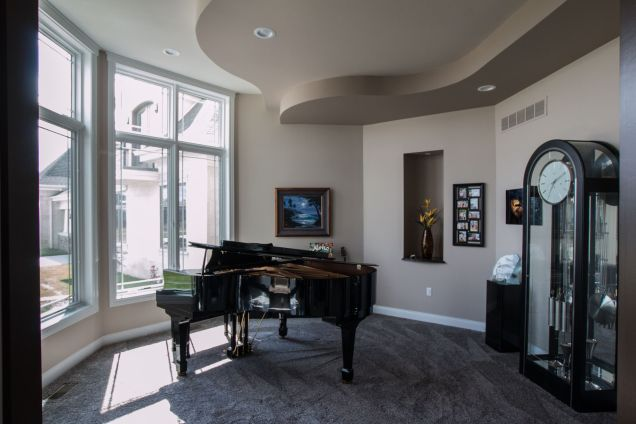 Grand piano in room with curved stepped ceiling details
