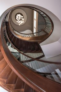 Looking up from the lower level through the center of a custom curved wood stairway