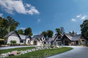 Front view of sprawling home with stone finish and timber accents