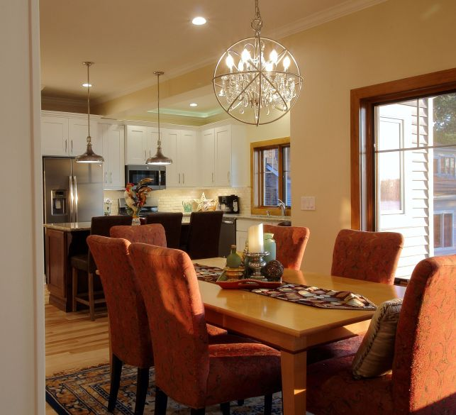 Upholstered chairs set around a dining room table with the kitchen beyond