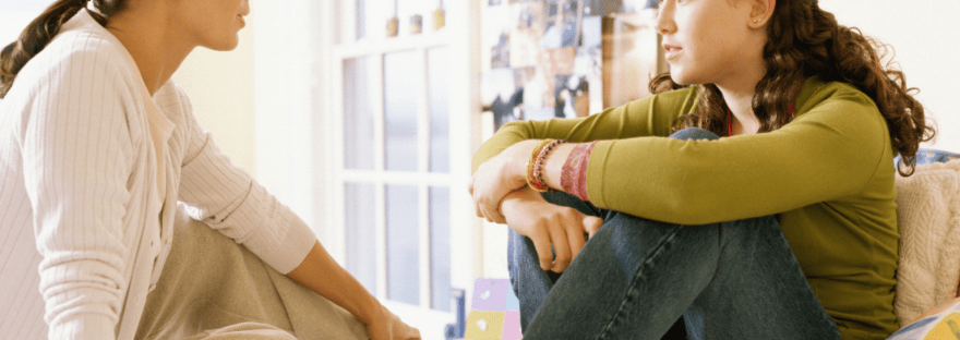 mom and daughter talking on bed, signs your teen wants therapy
