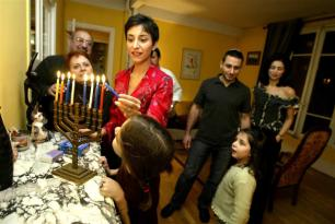 family lighting hanukah menorah together