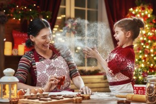 mother and young daughter baking christmas cookies