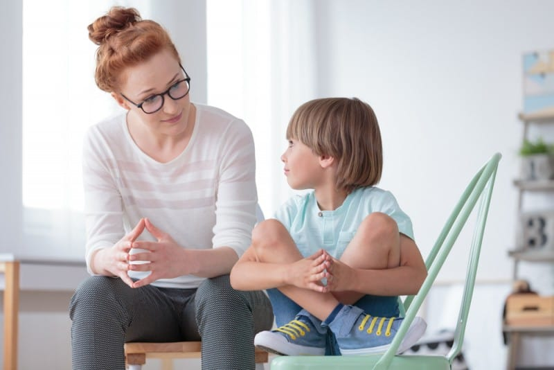 Red headed woman wearing glasses talking to a young boy sitting cross legged