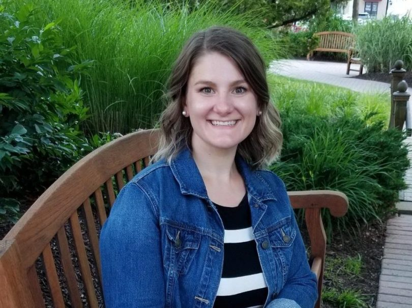 Emily Renda, executive functioning coach sitting on a brown bench in front of greenery