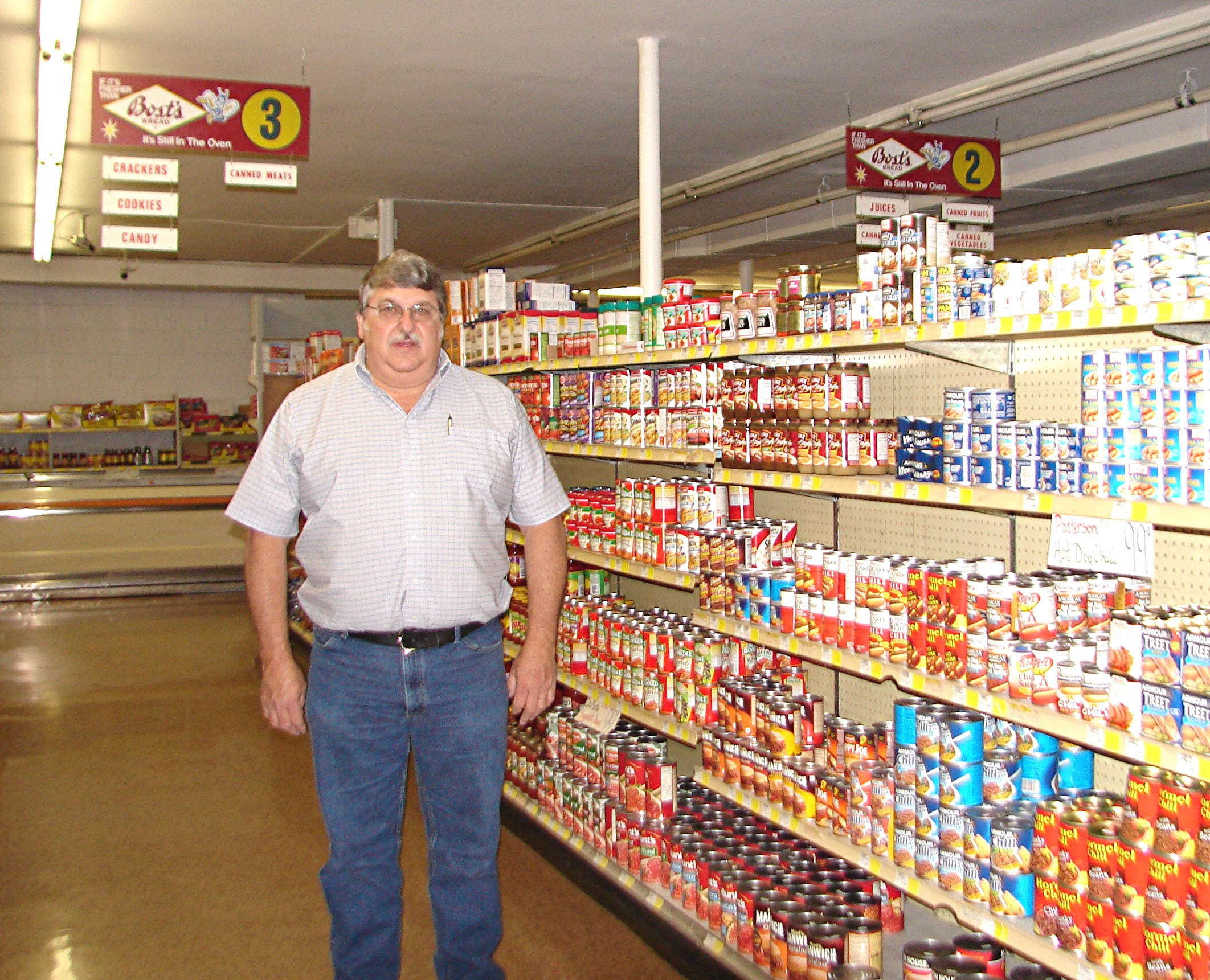 Bill Nichols in the aisle of John's Market today, under a vintage Bost Bread aisle sign