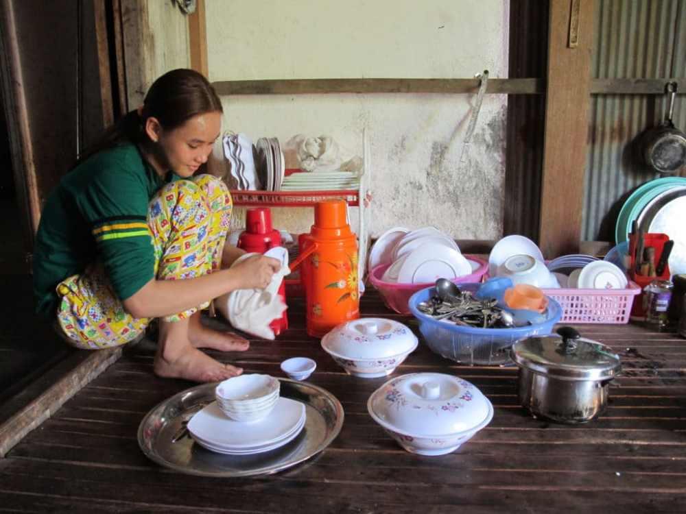 Femme au Cambodge sur l'île de Koh Trong qui fait la vaisselle