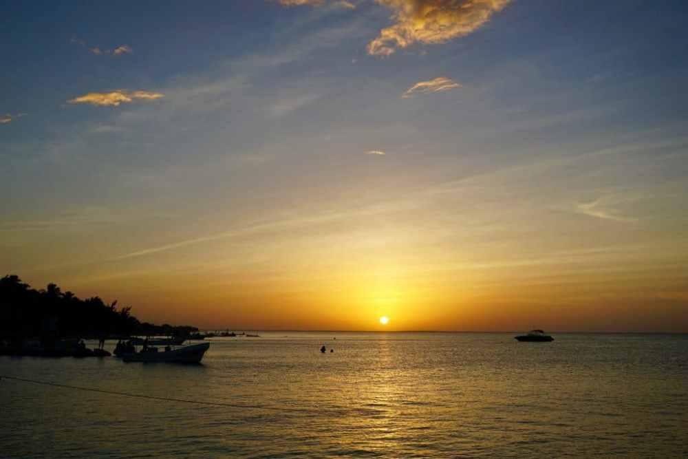 Coucher de soleil à Isla Holbox au Mexique avec bateaux de pêcheurs en avant-plan.