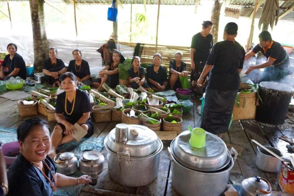 Des femmes et des hommes préparent le riz et la nourriture pour les convives ax funérailles dans le Toraja