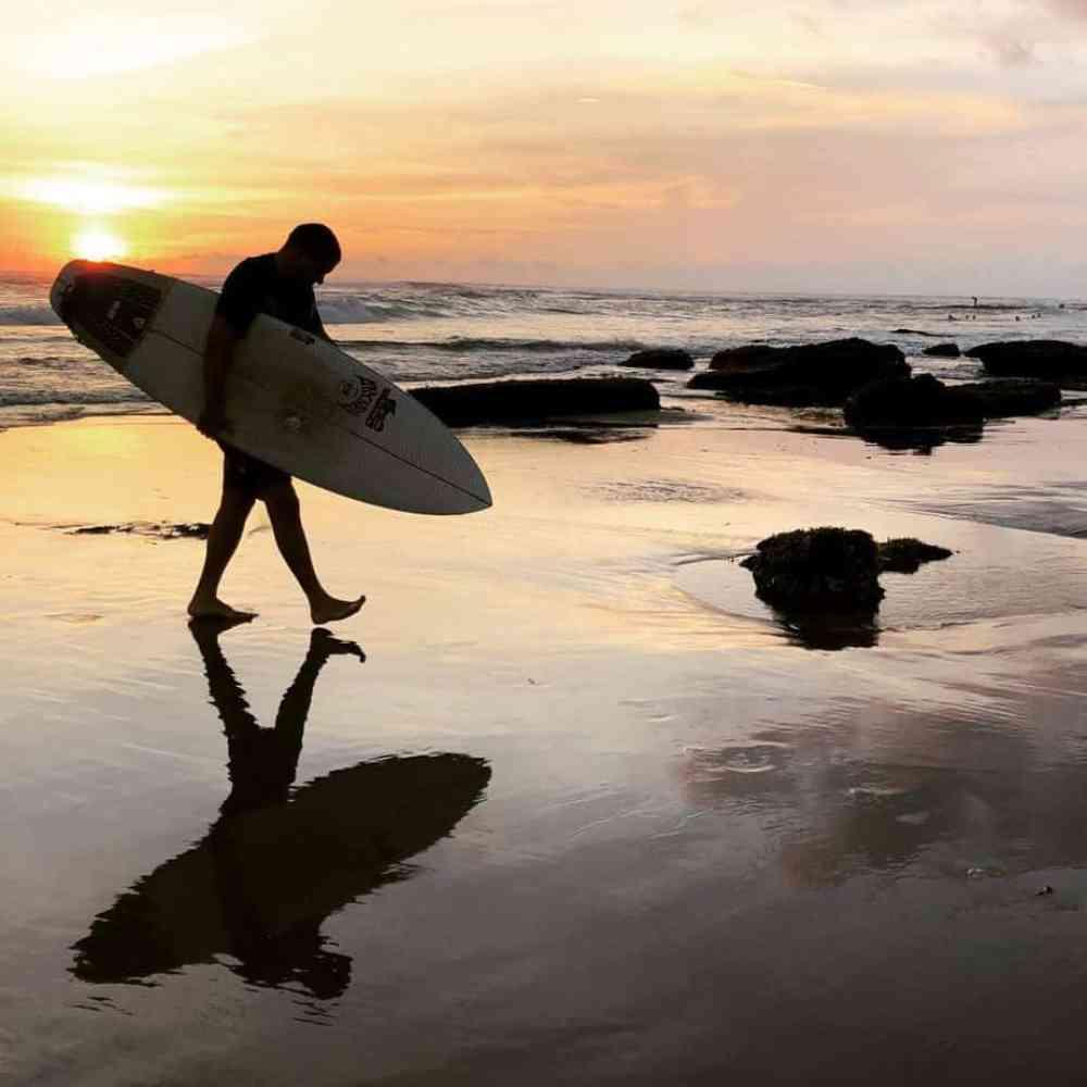 Surfer au coucher de soleil sur la plage Batu Bolong à Canggu Bali Indonésie