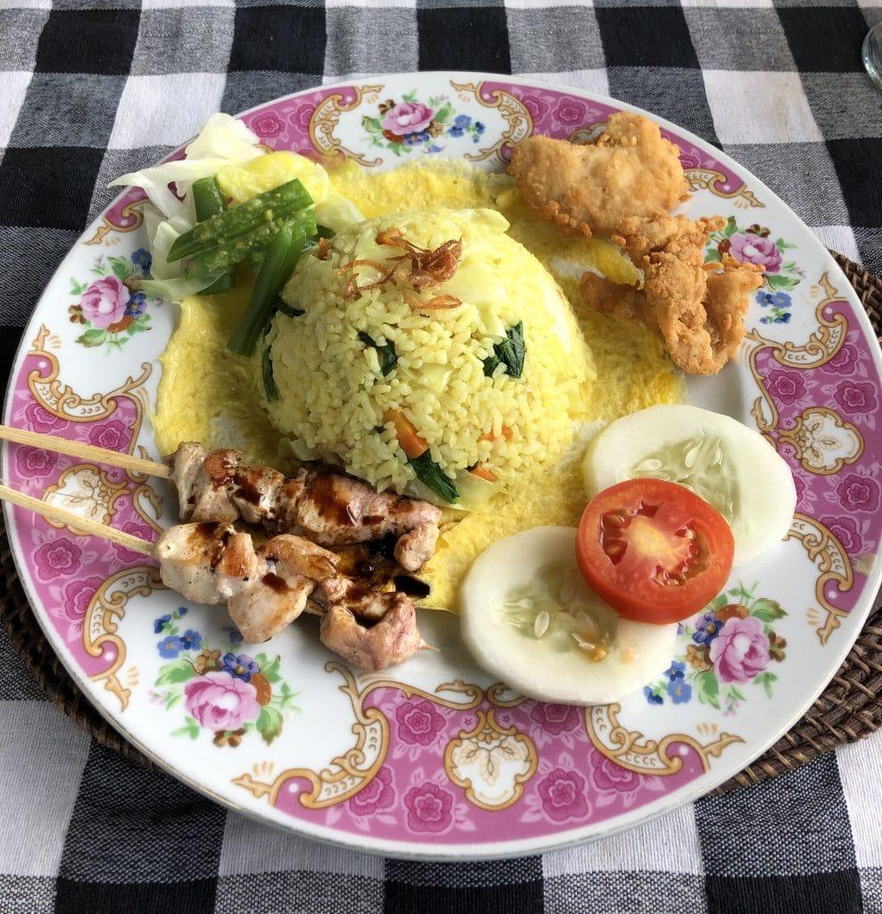 Repas indonésien de riz jaune avec brochettes de poulet
